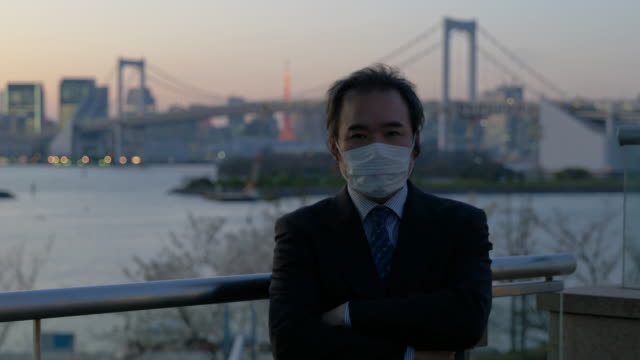 stockvideo's en b-roll-footage met middle-aged japanese businessman with a mask walking looking at the camera with the tokyo skyline in the background - mar