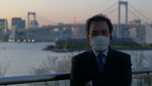 middle-aged japanese businessman with a mask walking looking at the camera with the tokyo skyline in the background (panning) - mar stock videos & royalty-free footage