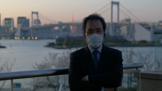 middle-aged japanese businessman with a mask walking looking at the camera with the tokyo skyline in the background - mar stock videos & royalty-free footage