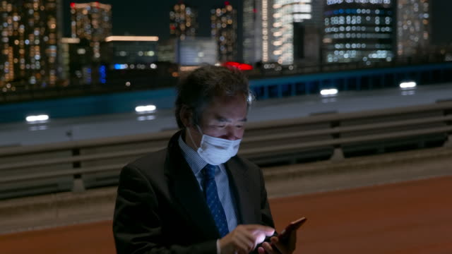 middle-aged japanese salaryman with a mask texting on his smartphone on the street at night in tokyo - mar stock videos & royalty-free footage
