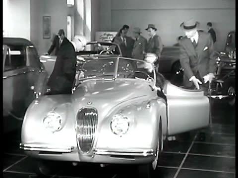 middleaged male escorting female in automobile showroom female getting into 1950 convertible jaguar luxury sports car couple talking w/ her sitting... - 1950年点の映像素材/bロール