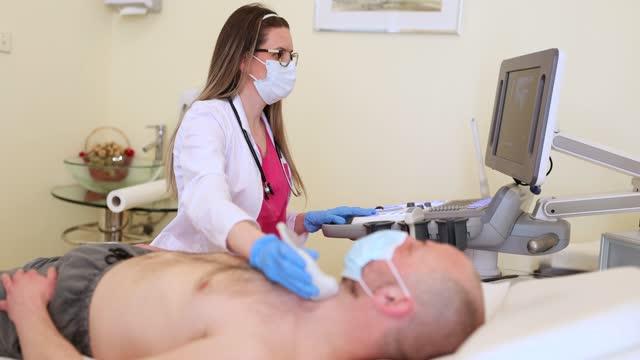 甲状腺超音波検査を受けた中年男性患者 - 腫瘍点の映像素材/bロール