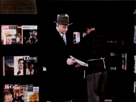 / MS middleaged man buys newspaper from news stand turns away from camera to reveal front page that he's reading Man buys newspaper from newsstand on...