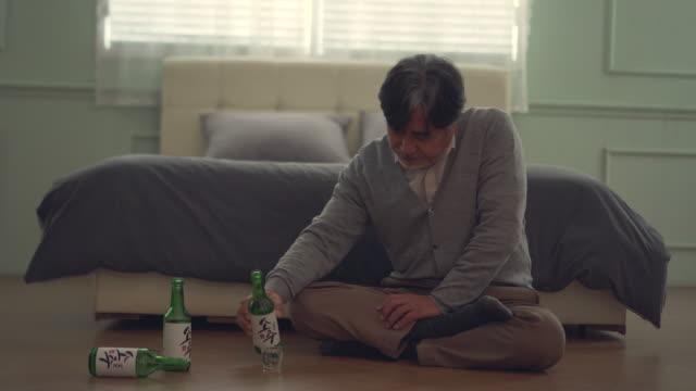 vídeos de stock e filmes b-roll de a middle-aged man drinking a bottle of soju (korean distilled spirits) in the room - cara para baixo