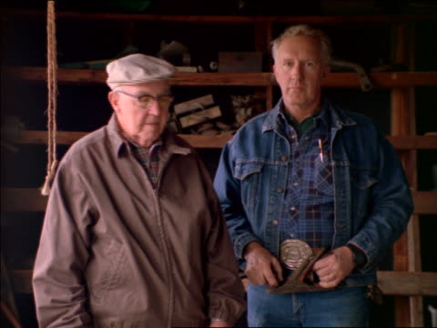 portrait middle-aged man in denim jacket + senior man with eyeglasses standing in workshop - denim jacket stock videos and b-roll footage