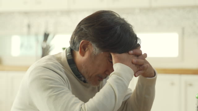 a middle-aged man looking tormented while holding his head - head in hands stock videos and b-roll footage