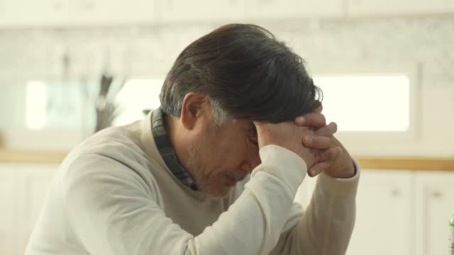 vidéos et rushes de a middle-aged man looking tormented while holding his head - se tenir la tête entre les mains