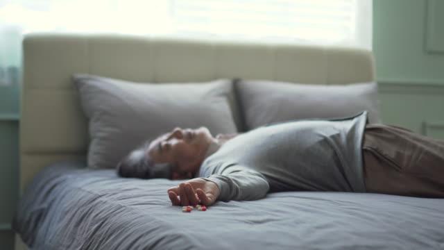 vídeos de stock, filmes e b-roll de a middle-aged man lying down on the bed with pills - só um homem maduro