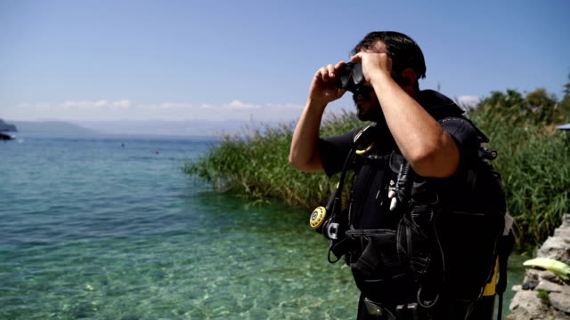 vídeos de stock, filmes e b-roll de homem de meia-idade coloca em uma máscara de mergulho e se preparando para mergulhar - diving suit