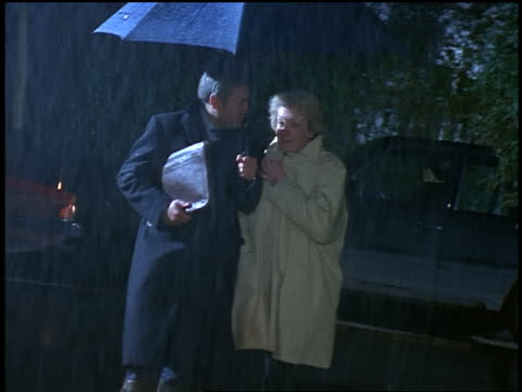 Middle-aged man + senior woman walking together in rain under blue umbrella toward camera