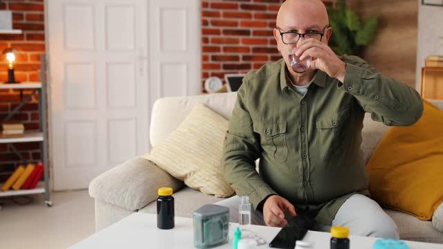 vídeos y material grabado en eventos de stock de un hombre de mediana edad se sienta en un sofá de su habitación y bebe su dosis diaria de medicinas y vitaminas. - modo de vida no saludable