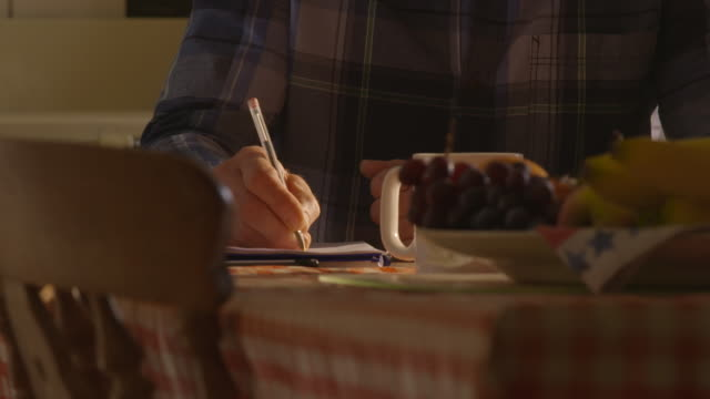 a middle-aged man sitting at a kitchen table writes on notepaper in red ballpoint pen. - messaggio video stock e b–roll