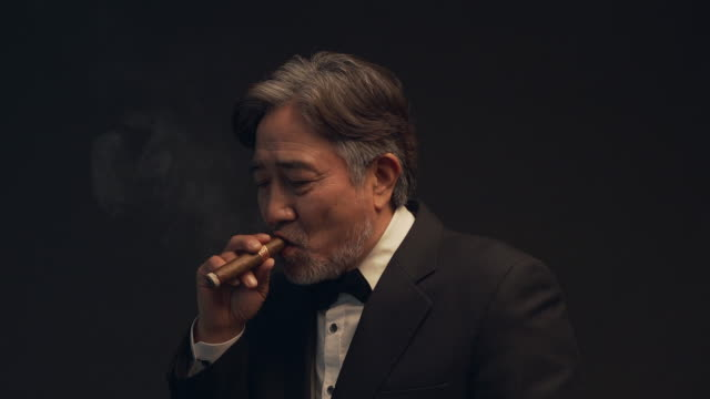 a middle-aged man smoking a cigar - sigaro video stock e b–roll