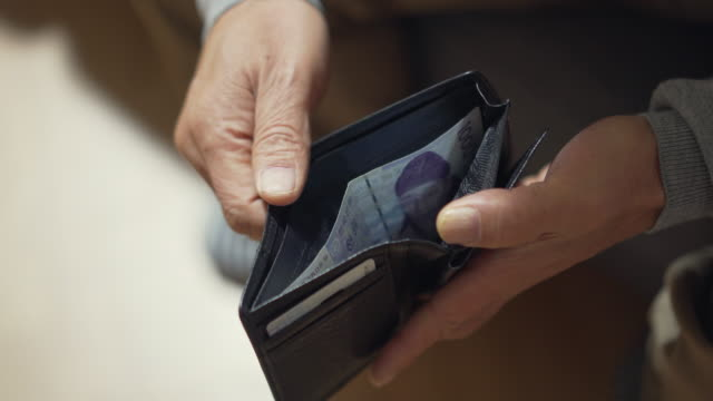 a middle-aged man's hand touching an empty purse - wallet stock videos & royalty-free footage