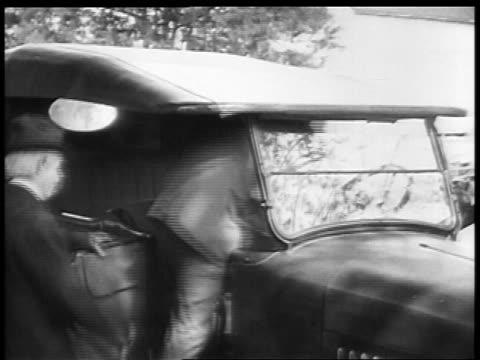 vidéos et rushes de b/w 1927 2 middle-aged men climbing into car / educational - seulement des hommes d'âge mûr