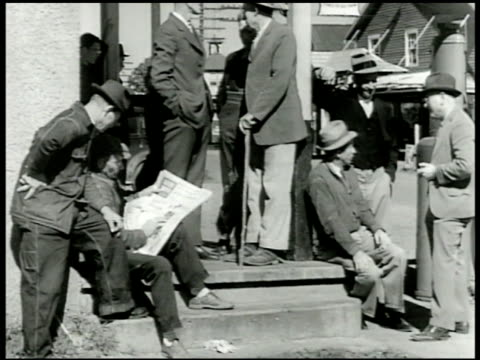 Middleaged men sitting standing on front porch of town building one male reading paper others talking Two males talking possibly farmers CU Newspaper...