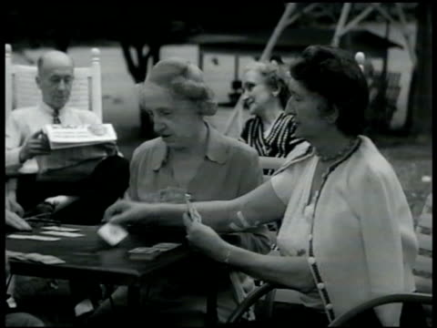 stockvideo's en b-roll-footage met middleaged older people sitting in row of rockers on porch playing cards at table outdoors socializing home vacation male painting house woman... - 1949
