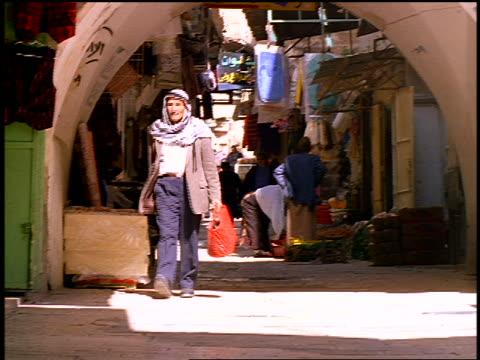 middle-aged palestinian man in kaffiyeh carrying bag walking thru outdoor market / jerusalem - palestinian stock videos & royalty-free footage