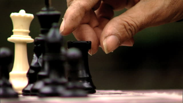 Middleaged weathered Hispanic or Latino male finger and thumb picking up black rook TRACKING Move across board placing game piece next to black pawn