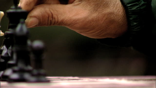middle-aged weathered hispanic or latino male finger & thumb pinching top of black rook game piece, picking up, sitting down, moving hand back.... - pinching stock videos & royalty-free footage