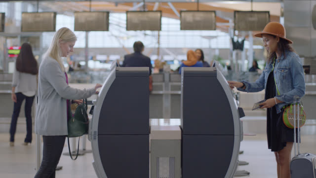 vídeos de stock e filmes b-roll de middle-aged woman and millenial woman check in using kiosks at airport terminal. - avião comercial
