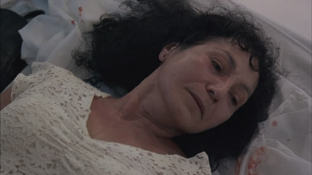 A middle-aged woman breathes deeply while lying on a bed.