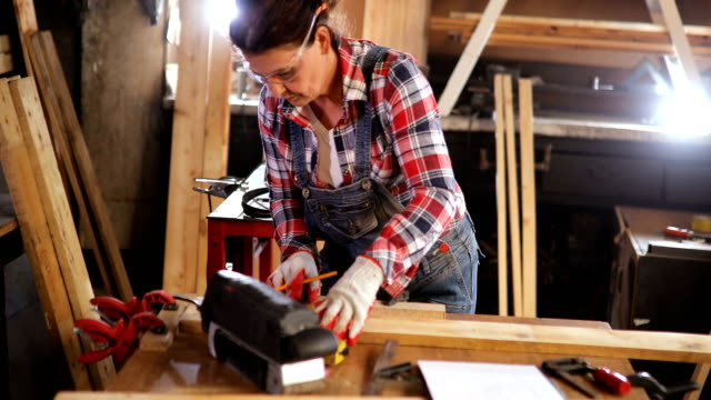 middle-aged woman carpenter works in carpentry workshop - mature women stock videos & royalty-free footage