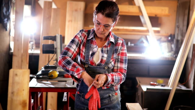 middle-aged woman carpenter works in carpentry workshop - solo una donna matura video stock e b–roll
