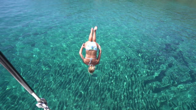 middle-aged woman does backflip off sailboat into clear, blue water - mature adult stock videos & royalty-free footage