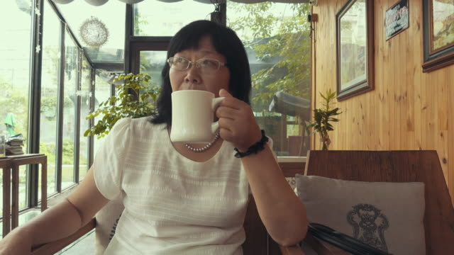 vídeos de stock, filmes e b-roll de middle-aged woman drinking coffee - planta de interior