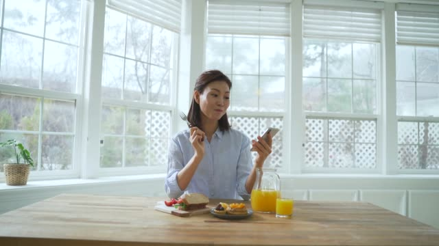 vídeos de stock, filmes e b-roll de a middle-aged woman eating and looking at a smartphone - sentar