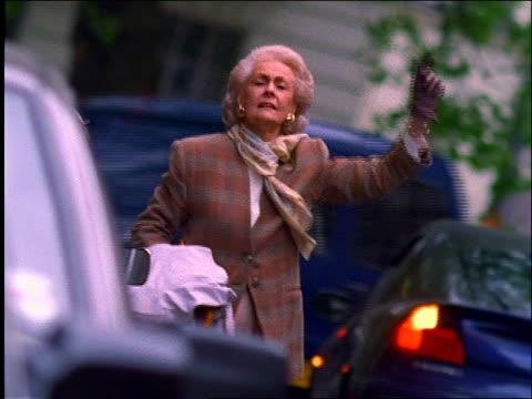 vídeos y material grabado en eventos de stock de middle-aged woman hailing taxi in traffic / london - inglaterra