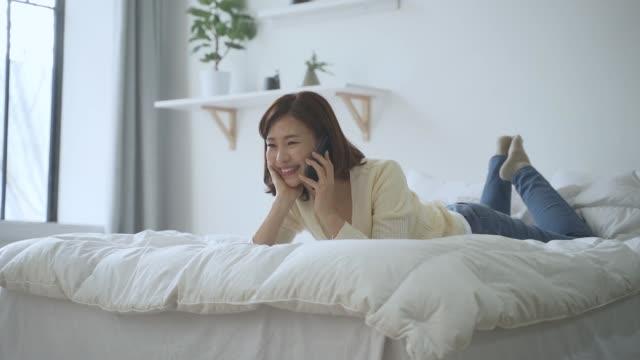 vídeos y material grabado en eventos de stock de a middle-aged woman lying on the bed and talking on the cellphone - tumbado boca abajo