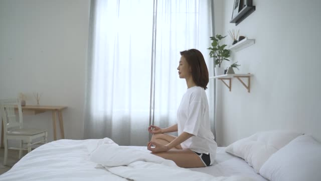 a middle-aged woman meditating in the morning - zen like stock videos & royalty-free footage