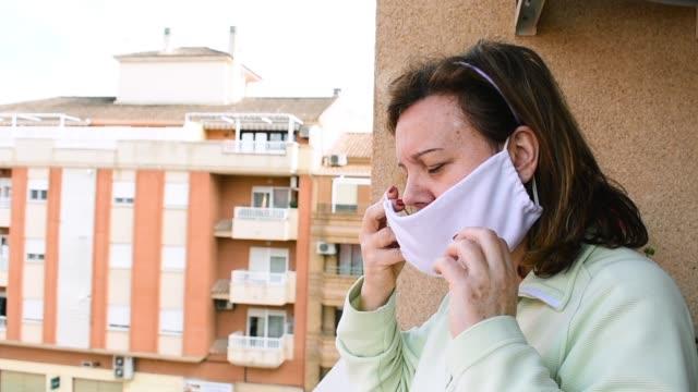 vídeos de stock e filmes b-roll de a middle-aged woman puts on a mask when she goes out - estado médico
