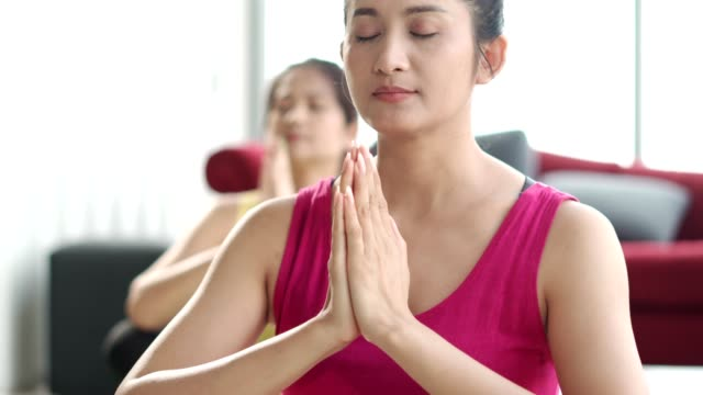 middle-aged woman relaxing during meditation exercise at a yoga class in living room - exercise room stock videos & royalty-free footage