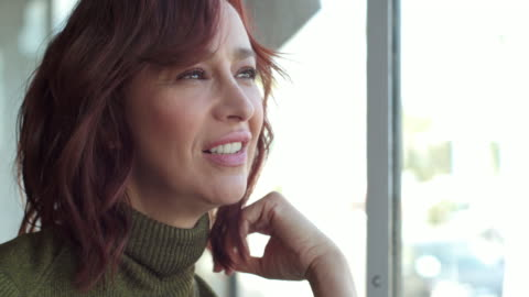 vídeos y material grabado en eventos de stock de middle-aged woman runs hands through red hair while looking out window, then rests hand at chin and turns toward camera smiling. - one mature woman only