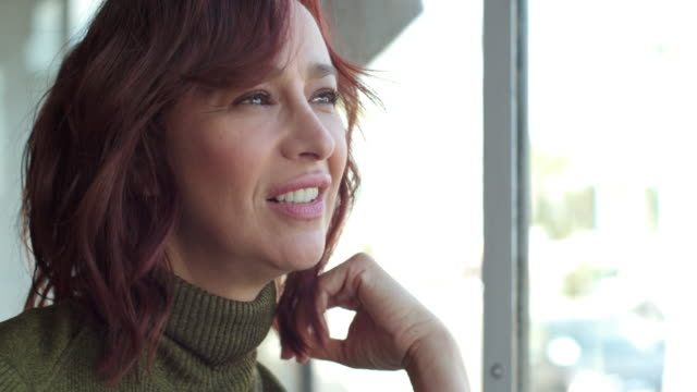 Middle-aged woman runs hands through red hair while looking out window, then rests hand at chin and turns toward camera smiling.