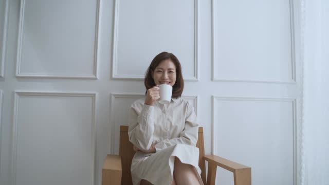 a middle-aged woman sitting down and smiling - chair stock videos & royalty-free footage