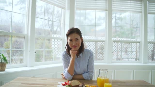 vídeos y material grabado en eventos de stock de a middle-aged woman smiling - zumo de naranja