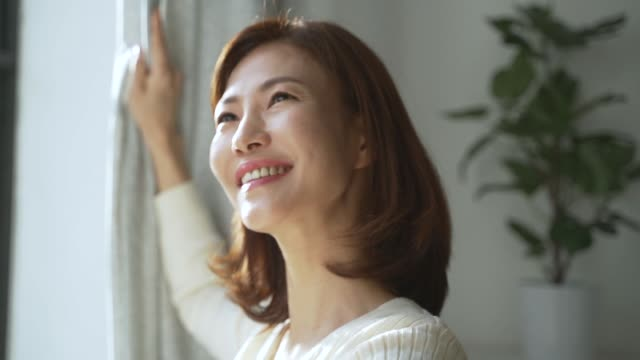 a middle-aged woman smiling with sunlight and looking at the outside - curtain stock videos & royalty-free footage