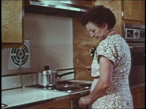 1960 middle-aged woman standing in kitchen turning knob on stove - 1960 stock videos & royalty-free footage