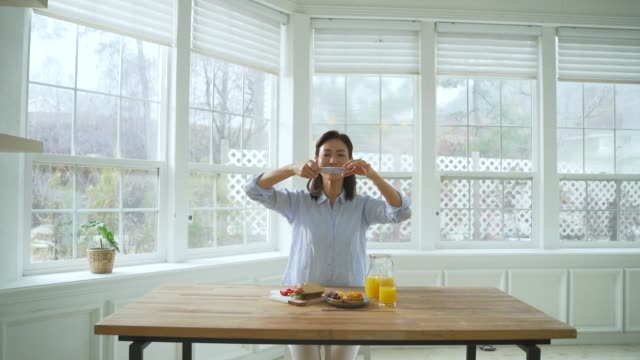 vidéos et rushes de a middle-aged woman taking a photo of breakfast with a smartphone - prendre une photo