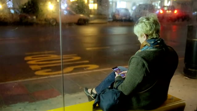 middle-aged woman waiting for the bus at the station and using mobile phone,night scene - stop sign stock videos and b-roll footage