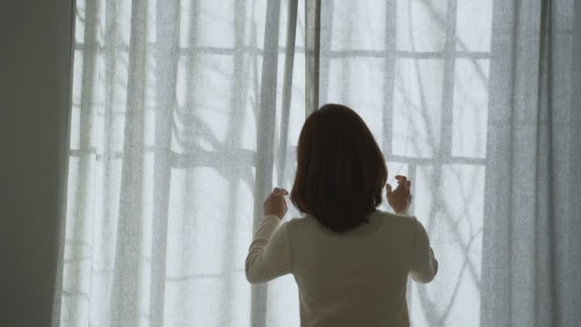 stockvideo's en b-roll-footage met a middle-aged woman waking up and drawing a curtain in the morning - gordijn