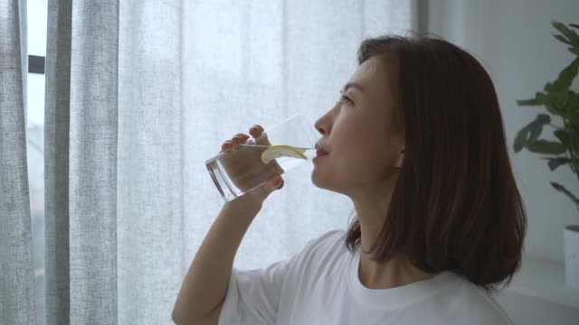a middle-aged woman waking up and drinking water in the morning - resting stock videos & royalty-free footage