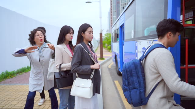 vídeos de stock, filmes e b-roll de a middle-aged woman who cuts in line to get on the bus - etiqueta conceito
