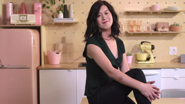 Middle-aged woman with black hair smiles as she sits on table and wraps hands around knee in kitchen.