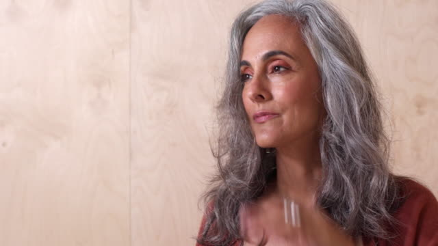 vídeos de stock e filmes b-roll de a middle-aged woman with gray hair looks off camera and rubs arms up shoulders as hair blows, against a wooden wall background. - cabelo grisalho