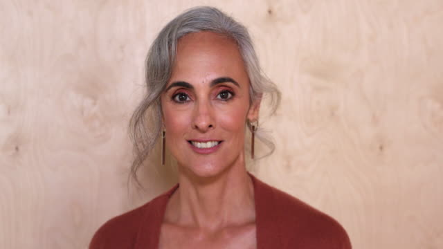 A middle-aged woman with gray hair opens eyes as she turns toward camera and smiles, against a wooden wall background.